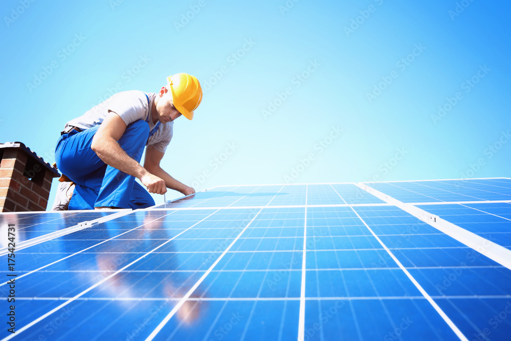 Fototapety, obrazy: Worker installing solar panels outdoors