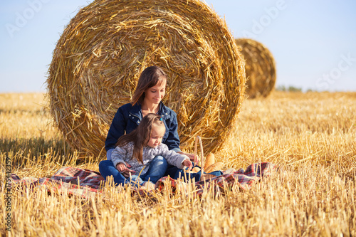 Fotomural Happy mother and 2 year old girl next to hay bales in harvested field