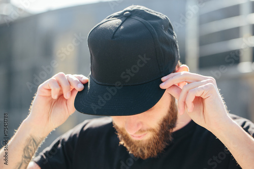 Fototapeta Hipster handsome male model with beard  wearing black blank  baseball cap  with