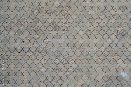 Obraz The texture of a rhythmic mosaic made of concrete tiles. Background image of a large area of old and damaged gray tiles - fototapety do salonu