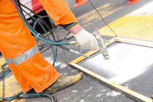 Man worker remarking pedestrian crossing lines on asphalt
