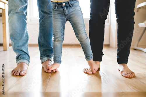 Photo Beautiful young family. Bare feet of mother, father and daughter