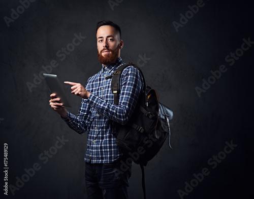 Fototapeta A man holds tablet PC and a backpack. obraz na płótnie