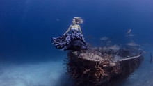 Underwater View Of Woman In Purple Dress Poised By Shipwrecked Boat, Bahamas