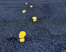 Yellow Footprint Signs On An Asphalt Road. Painted Footprints Show The Way