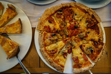 Delicious Slice Of Homemade Baked Pizza On White Plate With Partial Of Pies On Greek Breakfast Buffet Table