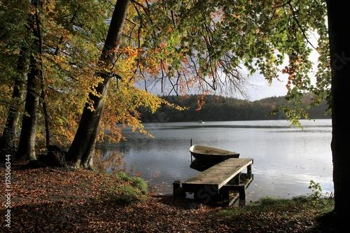 Plakat malownicze kładka z łodzi nad jeziorem jesienią