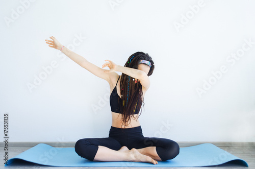 Beautiful young sporty girl with dreadlocks doing yoga  Sport