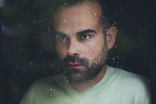 Portrait Of A Man Standing At The Window Watching The Rain