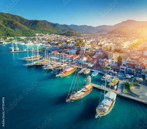 Photo Stands Port Aerial view of boats and beautiful architecture at sunset in Marmaris, Turkey. Colorful landscape with boats in marina bay, sea, city, mountains. Top view from drone of harbor with yacht and sailboat