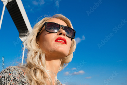 Photo Portrait of a beautiful young girl in sunglasses looking afar, against the blue
