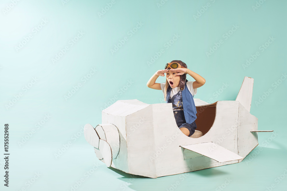 Fototapety, obrazy: Little cute girl playing with a cardboard airplane. White retro style cardboard airplane on mint green background . Childhood dream imagination concept .