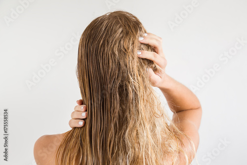 Woman touching her wet blonde hair after shower on the gray background Fototapeta