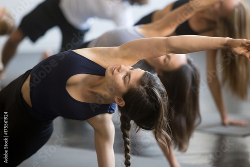 Poster Ecole de Yoga Group of young sporty people practicing yoga lesson with instructor, stretching in Bending Side Plank exercise, Vasisthasana pose, working out, indoor close up image, studio, smiling woman in focus