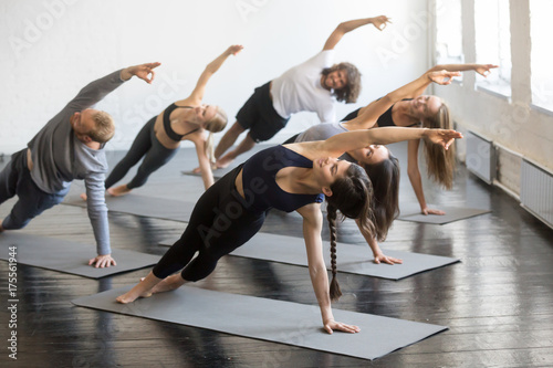 Poster Ecole de Yoga Group of young sporty people practicing yoga lesson with instructor, stretching in Bending Side Plank exercise, Vasisthasana pose, working out, indoor studio image. Wellbeing, wellness concept