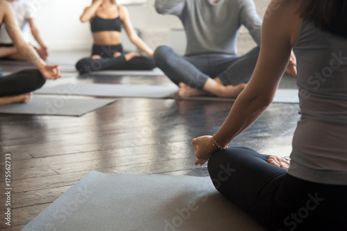 Poster Ecole de Yoga Young sporty people practicing yoga lesson with instructor, sitting, making Alternate Nostril Breathing, nadi shodhana pranayama exercise, working out, close up image. Wellbeing and wellness concept