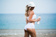 young beautiful sports girl posing with a bottle in his hand on the beach