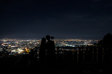 Panorama Of The City From The Viewpoint With Silhouette Tourists At Doi Suthep. Chiangmai Night View, Thailand.