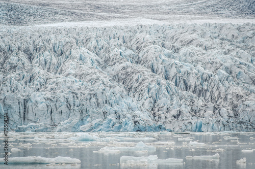 Plakat Lodowiec kończący się laguną ze spadającymi kawałkami gór lodowych.