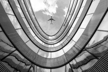Flying Airplane And Modern Architecture Building, Low Angle Black And White Abstract Looking Picture