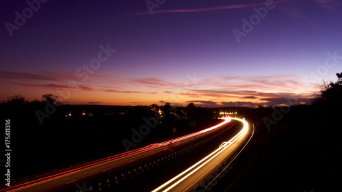 Foto op Aluminium Nacht snelweg Light trails on a clear evening in October, under a harvest moon