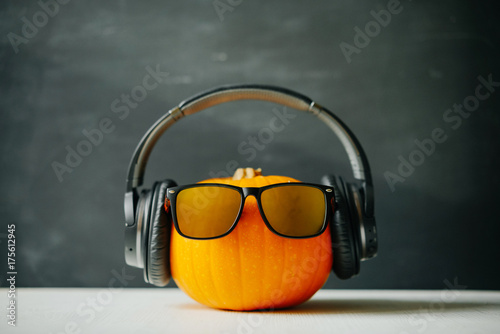 Papiers peints Magasin de musique Halloween pumpkin with glasses and headphones on a black chalkboard background.