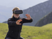 Woman Practicing Karate Moves With Virtual Reality Glasses On Mountain