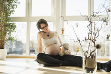 Pregnant Woman With Teddy Bear Sitting On Floor