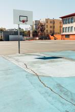 Solitary Basketball Hoop On Light Blue Asphalt Court In School Playground