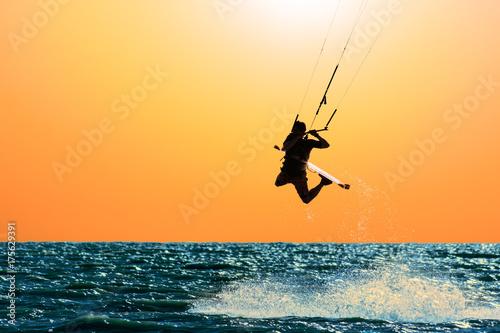 Silhouette of kitesurfer on the background of orange sunset