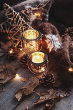 Wool Mittens With Candles And Leaves On Table