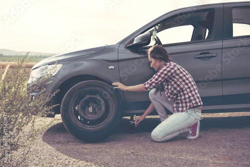 Zdjęcie XXL Piękna młoda kobieta zmienia opony na jej samochodzie