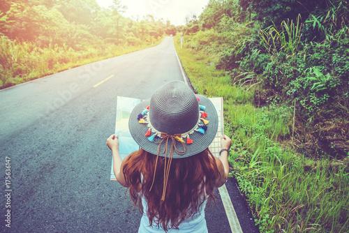 Plakat Azjatyckie kobiety podróżują w czasie wakacji. Rzuć okiem na mapę na wiejskiej drodze w środku natury. Tajlandia