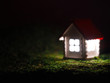 Blured toy house with luminous windows in the dark. Model little white home with a red roof at night