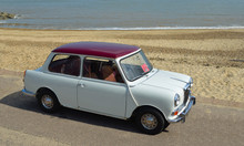 Classic Cream & Red Wolseley Mini  Car  Parked On Seafront Promenade With Sea In Background.