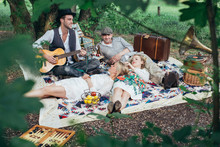 Retro Picnic - Four Friends Enjoying Themselves On A Spring Day In Green Countryside