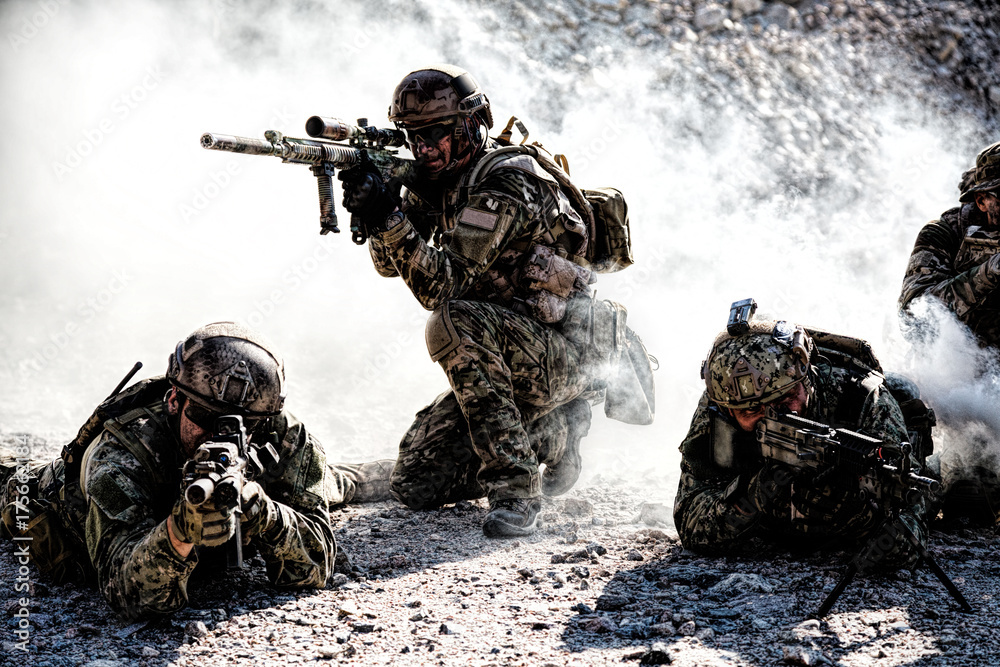 Fototapeta Team squad of special forces in action in the desert among the rocks covered by smoke screen