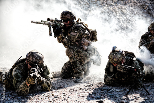 Team squad of special forces in action in the desert among the rocks covered by Obraz na płótnie