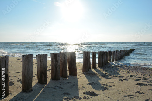 In de dag Inspirerende boodschap Holz buhnen am Strand und im Wasser an der Nordsee beim Sonnenuntergang