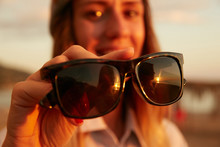 A Girl Showing Sunglasses To T...