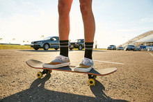 Legs Of A Girl Standing On A Skateboard On A Parking In Sunset - Static