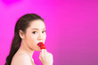 Leinwanddruck Bild - Young Asian woman kissing strawberry isolated in pink background.