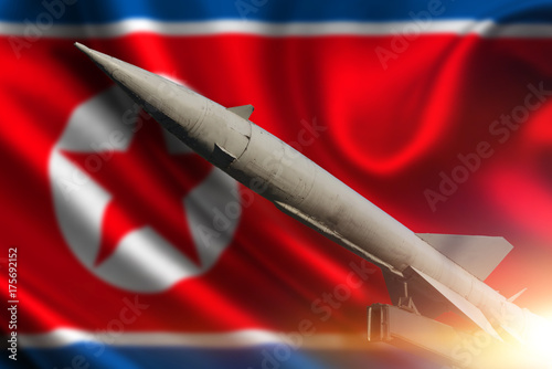 Fototapeta Rakieta na tle Flaga Korei Północnej. Broń masowego rażenia. Pociski z głowicami. Broń jądrowa, broń chemiczna.