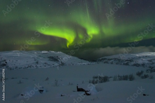 The snow covered the hills and in the sky the stars and the aurora borealis Canvas-taulu