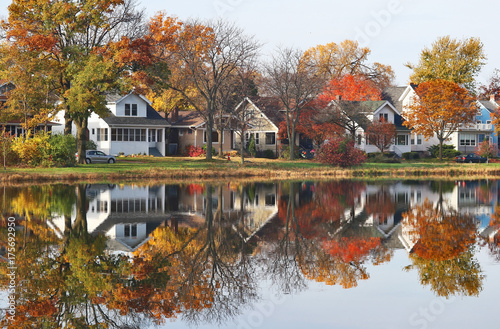 Autumn in a city background. Fall cityscape with private houses neighborhood along a pond. Colorful trees and houses reflected in a water. Midwest USA, Wisconsin. Classic american middle class homes.