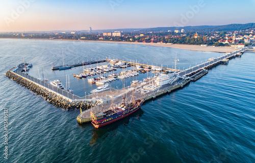 Zdjęcie XXL Sopot Resort w Polsce. Drewniane molo (molo) z mariną, jachtami, pirackim statkiem turystycznym, infrastrukturą plażową i wakacyjną. Widok z lotu ptaka na wschód słońca