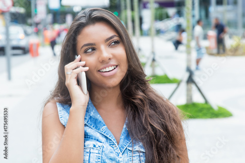 Zdjęcie XXL Roześmiany łaciński żeński nastolatek przy mądrze telefonem