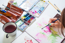 Close-up Of A Woman Artist Paints  Watercolor Drawing Of A Pink Flower Of A Peony And A Dog Rose In The Album For Drawing On A White Table, Beside Lies A Watercolor Palette And A Cover With Tassels