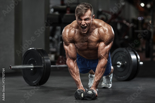 Poster Fitness Muscular man working out in gym doing exercises, strong male naked torso abs