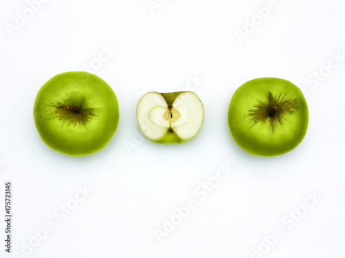 Poster Légumes frais Green apples Top view Fresh granny smith Two whole apples and one half of apple are lying horizontally in a row on a white background Flat lay mockup with text space.